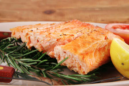 served fish: roast salmon fish over glass plate over wood photo