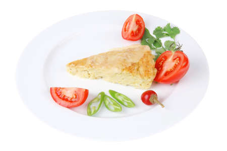 meatless: food : vegetable casserole triangle on white plate with pepper and tomatoes isolated over white background
