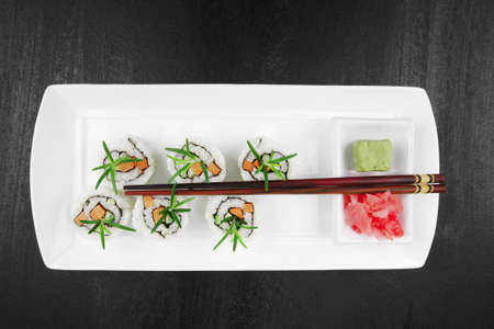 Maki Sushi - California Roll with Cucumber , Cream Cheese and Salmon inside. Served with wasabi and ginger . on long white plate over black table Stock Photo - 10773573