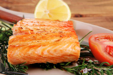 roast fish: hot grilled salmon over glass plate on over wooden table photo