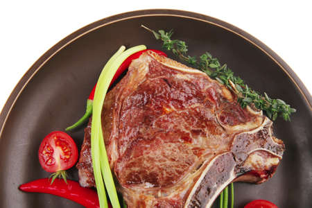 meat food : roast rib on dark dish with thyme pepper and tomato isolated over white background photo