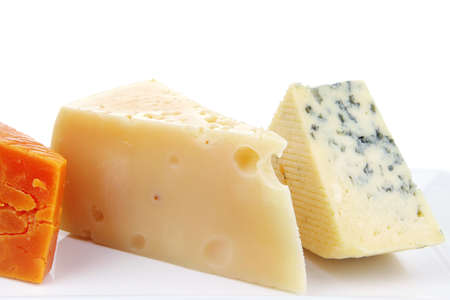 old blue stilton roquefort with orange cheddar and yellow parmesan on plate with isolated over white background photo