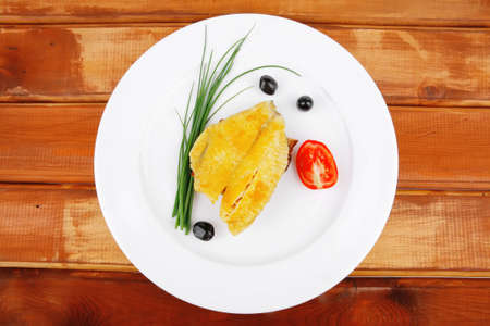 roasted fish fillet with tomatoes,chives and bread on plate over wooden table Stock Photo - 10824387