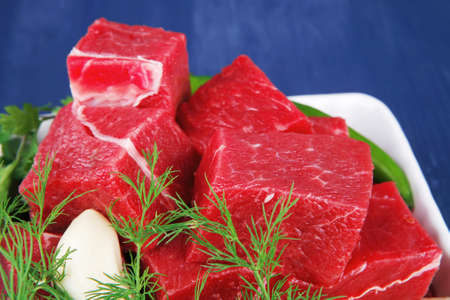 uncooked fresh beef meat chunks on white bowls with green hot peppers and vegetables serving over blue wooden table photo