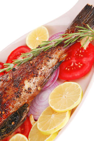 whole fried bass on plate, served with lemons and tomatoes photo