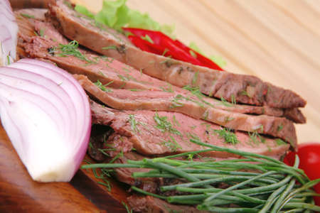 beef slices on wooden plate with peppers on wood Stock Photo - 10843413