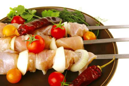 fresh raw chicken kebabs served on dark plate photo