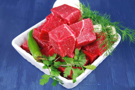 circular muscle: raw fresh beef meat slices in a white bowls with dill and green hot peppers serving over blue wooden table