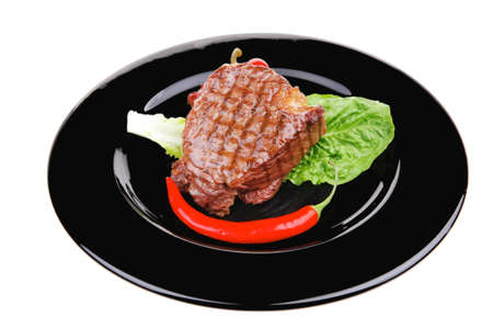 meat savory : beef grilled and garnished with green lettuce and red chili hot pepper on black dish isolated over white background photo