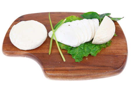 mediterranean dairy  : fresh raw white soft greek feta cheese round and slices on wooden plate isolated over white background photo