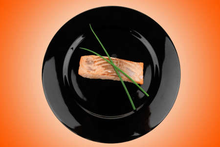 savory fish portion : norwegian salmon fillet roasted with green chinese onion, on black dish isolated over white background Stock Photo - 10885616