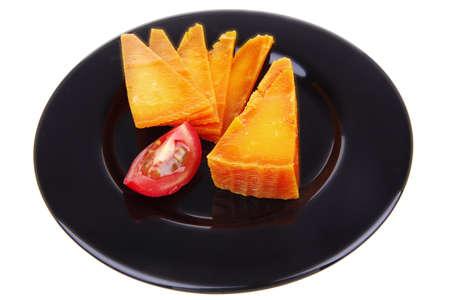 tabla de quesos: naranja, queso cheddar envejecido deliciosa tajada de queso con una rodaja de tomate y en un plato negro aislado sobre fondo blanco