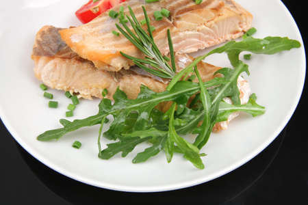 savory sea fish : roasted salmon fillet garnished with green rocket leaves and tomatoes on black dish isolated over black background photo