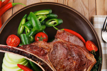 savory : grilled spare rib on dark dish with thyme pepper and tomato on wooden table Stock Photo - 10889562