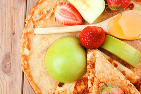 sweet food : big thin pancake with honey strawberries and apple on wooden table Stock Photo - 10889481