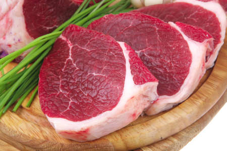 carniceria: carnicer�a: carne fresca cruda costillas de cordero grande y filete listo para cocinar con materia verde en el plato de madera aislada sobre fondo blanco