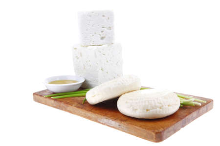 dairy product : fresh raw white soft greek feta cheese cubes and round on wooden plate isolated over white background photo