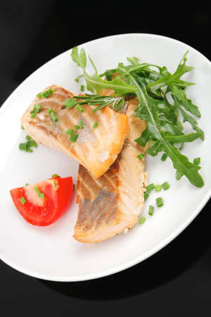 healthy fish cuisine  : baked pink salmon steaks garnished with tomatoes and rocula on white dish isolated over black background Stock Photo - 10893362