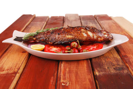fryed: main course: whole fryed sunfish on wooden table with lemons and peppers Stock Photo