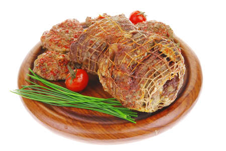 served roast meat on wooden plate with tomatoes photo