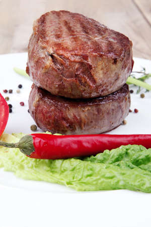 grilled beef fillet pieces with thyme , red hot chili pepper and tomato on white plate over wood Stock Photo - 10916196