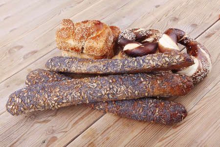 mix of fresh homemade baguettes , pretzels and wheat loafs, on wooden table photo
