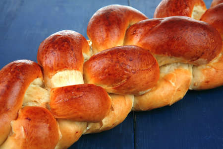 jewish cuisine: sweet bread : golden challah over blue wooden plate Stock Photo