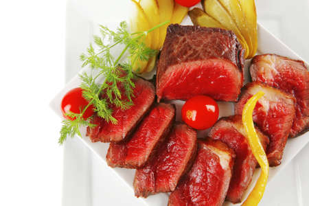 underdone beef meat with vegetables on white plate photo