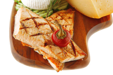 pink grilled salmon on wooded plate over white photo