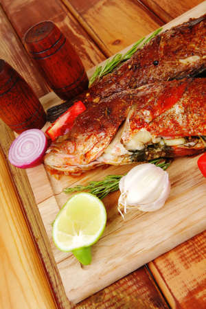 sunfish: roast golden fish served on wooden table with lemon tomatoes and salad