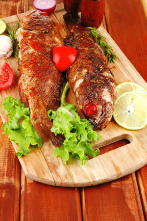 castors: roasted sea fish and castors on wood with tomatoes, lemon and green lettuce salad . shallow dof