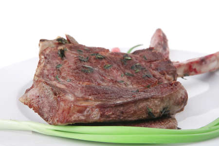boned: served main course: boned roasted lamb ribs served with green chives and red chili peppers on white dish isolated over white background