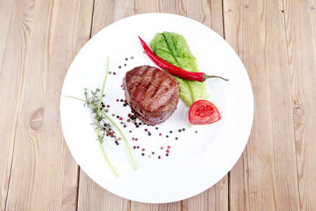 grilled beef fillet pieces with thyme , red hot chili pepper and tomato on white plate over wood photo