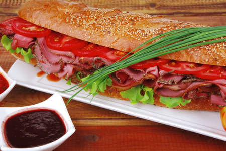 sandwich on plate : french baguette with smoked sausage on white plate over wooden table Stock Photo - 11081216