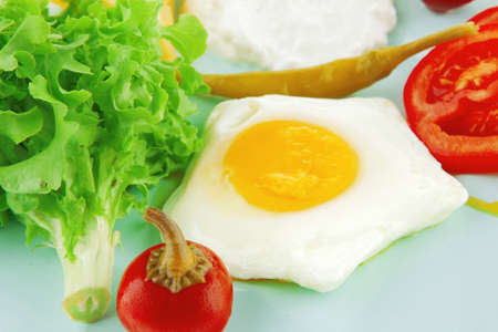 curd: fried eggs with curd and salad on blue plate Stock Photo