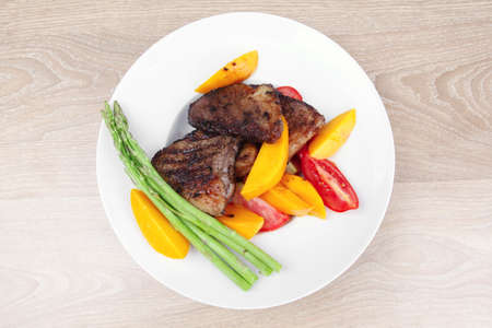 meat food : grilled red beef fillet with mango tomatoes and asparagus , served on white dish over wooden table Stock Photo - 11081158