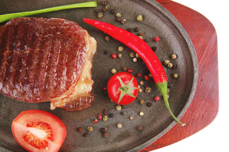 main entree : platter of roasted beef steak served with hot cayenne peppers cherry tomato green chives on metal pan isolated over white background photo