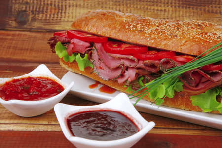 sandwich on plate : french long baguette with smoked chicken sausage on plate with sauces over wood photo