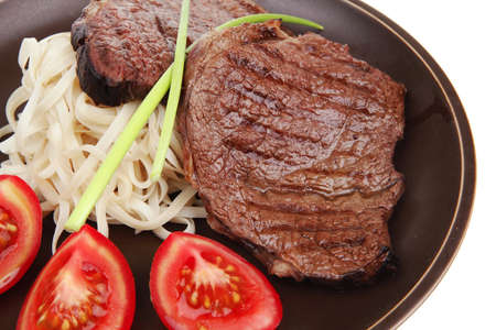 close-up of juicy sirloin beef with pasta tomatoes and green onion on dark dish isolated over white background photo