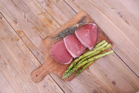 prime fillet meat : dry raw beef on cutting board with asparagus , thyme bundle , color peppercorn mix and red paprika powder mixed with dry spices over wooden table ready to cooking photo