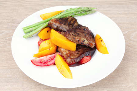 meat food : rare medium roast beef fillet with mango tomatoes and asparagus , served on white dish over wooden table Stock Photo - 11129903