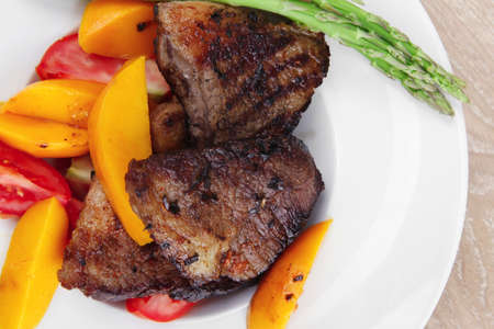 meat food : rare medium roast beef fillet with mango tomatoes and asparagus , served on white dish over wooden table Stock Photo - 11129910
