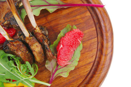 main portion : grilled ribs on woden plate isolated over white background with salad leaves and red grapefruit photo