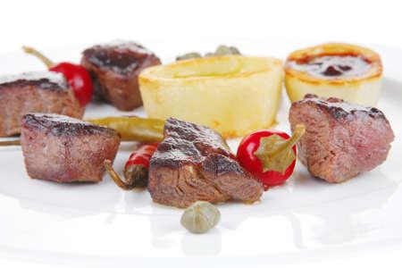 european food: europeo de alimentos: la carne de vacuno a la parrilla en plato de porcelana blanca aislados en fondo blanco pimienta caliente, las alcaparras y las salsas