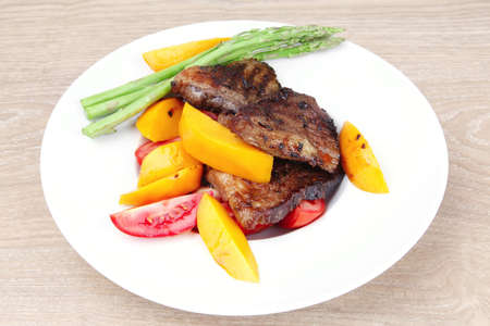 meat food : rare medium roast beef fillet with mango tomatoes and asparagus , served on white dish over wooden table Stock Photo - 11149876