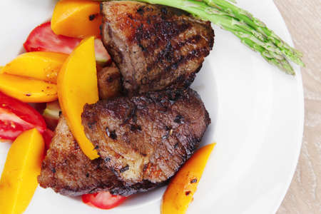 meat food : rare medium roast beef fillet with mango tomatoes and asparagus , served on white dish over wooden table Stock Photo - 11149881