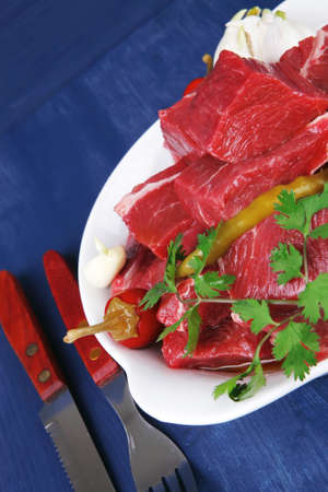 slices of raw fresh beef meat fillet in a white bowls with garlic and red peppers serving on blue table with cutlery photo