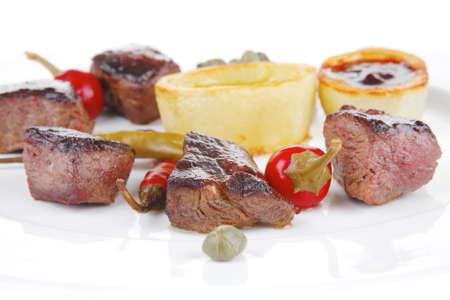 european food: europeo de alimentos: carne de vacuno a la parrilla en plato de porcelana blanca aislados en fondo blanco pimienta caliente, las alcaparras y las salsas Foto de archivo