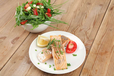 savory fish portion : roasted norwegian salmon chunks and vegetable salad on white dish over wooden table photo