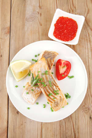 healthy sea food : roasted pink salmon fillet on white dish with red caviar over wooden table photo